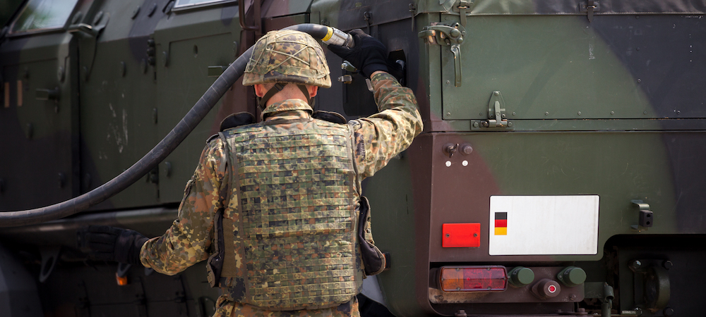 Military troops fueling up vehicle on base with access to safe miliatry storage building for flammable liquid compliance