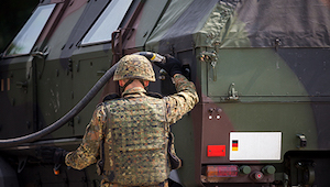 Military man in uniform filling a camo military vehicle with gasoline