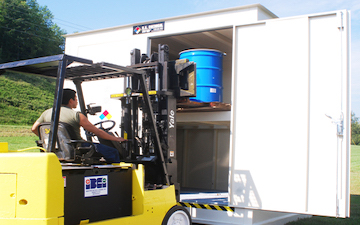 man using forklift to put flammable liquids into appropriate storage unit