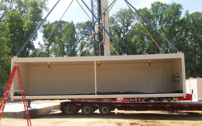 A modular chemical storage building from U.S. Chemical Storage is loaded to a truck.