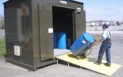 Man wheeling barrel of chemicals into hazmat storage locker